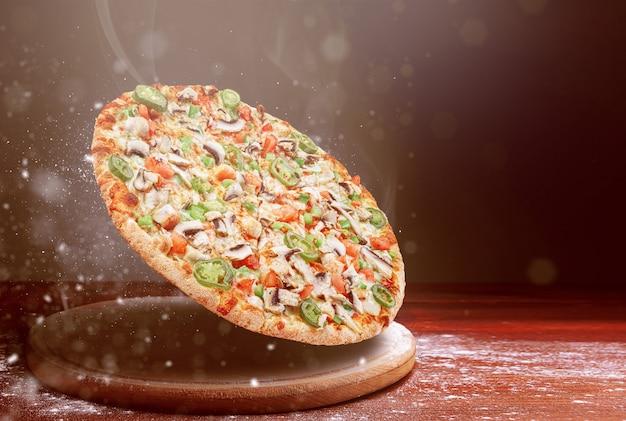 Klassieke pizza op een donkere houten tafeloppervlak en een beetje bloem. pizza restaurant menu concept
