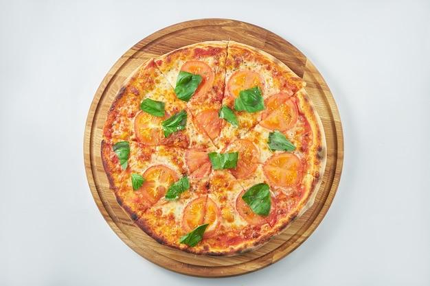 Klassieke pizzamargarita met rode saus, tomaten en basilicum op een houten dienblad. witte achtergrond. italiaanse keuken