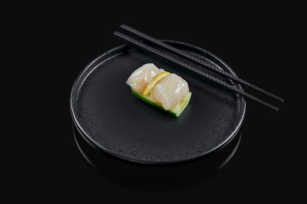 Klassieke rauwe coquille sashimi met komkommer op een stijlvolle zwarte keramische plaat op een zwarte ondergrond. japans traditioneel eten. foto voor het menu
