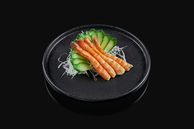 Klassieke rauwe garnalen of garnalen sashimi met komkommer en daikon radijs op een stijlvolle zwarte keramische plaat op een zwarte ondergrond. japans traditioneel eten. foto voor het menu