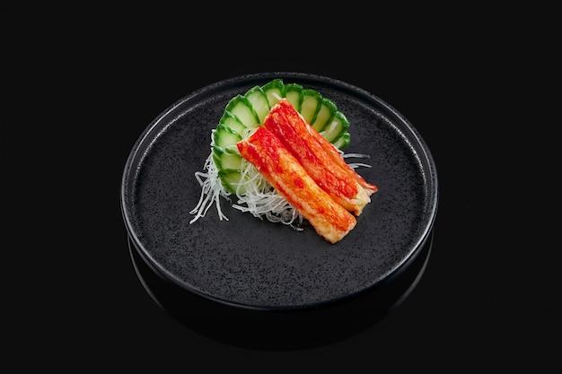 Klassieke rauwe krab sashimi met komkommer en daikon radijs op een stijlvolle zwarte keramische plaat op een zwarte ondergrond. japans traditioneel eten. foto voor het menu