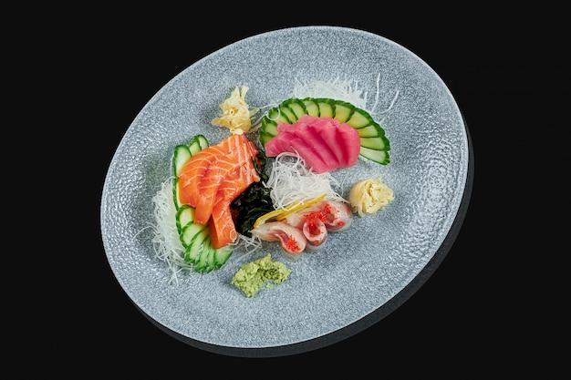 Klassieke rauwe set van sashimi zalm, zeebaars en tonijn met komkommer en daicon op een stijlvolle zwarte keramische plaat op een zwarte ondergrond. japans traditioneel eten. foto voor het menu