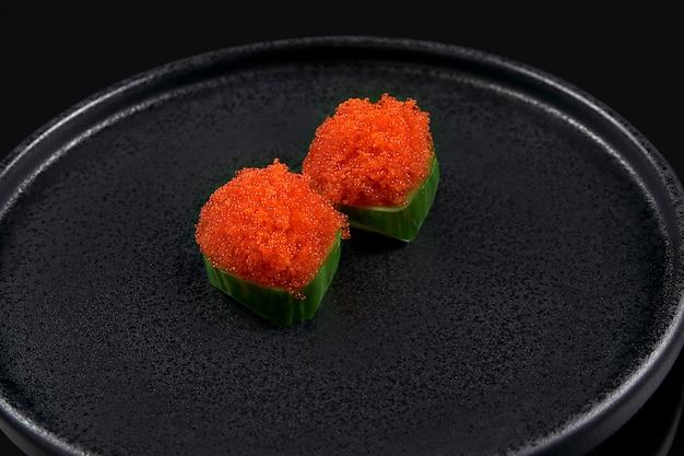 Klassieke rauwe tobiko kaviaar sashimi met komkommer op een stijlvolle zwarte keramische plaat op een zwarte ondergrond. japans traditioneel eten. foto voor het menu
