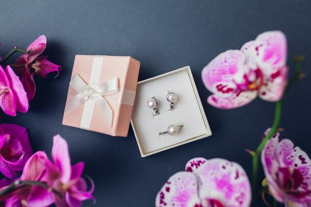 Klassieke retro stijlvolle sieraden. zilveren ring oorbellen met parels in geschenkverpakking met paarse orchidee. modieuze accessoires