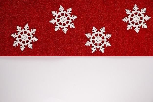 Klassieke rode kerstmis siert decoratieachtergrond met horizontaal schitter sneeuwvlokken.