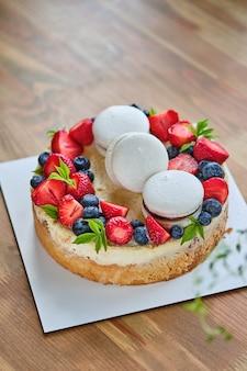 Klassieke romige cheesecake met aardbeien en bosbessen op een houten tafel. cheesecake gegarneerd met verse bessen en macaron. dessert voor een cadeau en verjaardag. heerlijk en mooi dessert.