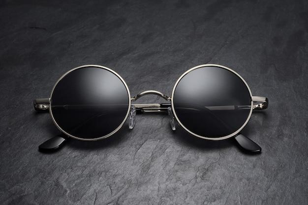 Klassieke ronde grijze gun metal zonnebril op op zwarte leisteen achtergrond