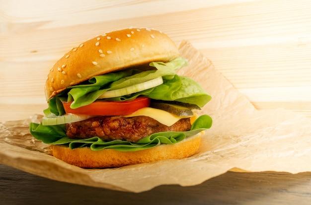 Klassieke rosbiefburger met verse uien, tomaten, slasla en sappige kotelet. rundvleesburger met medium zeldzame biefstuk op kraftpapier