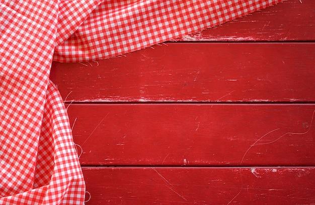 Klassieke roze geruite stof of tafelkleed op oude rode houten tafel met kopieerruimte