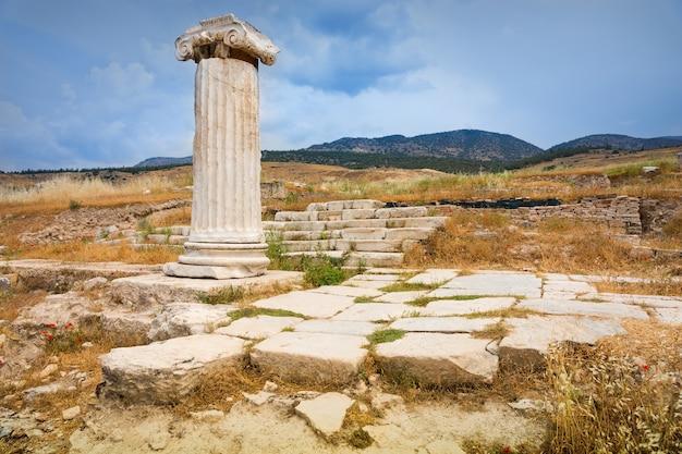 Klassieke ruïnes op het bergachtige griekse platteland met grote straatstenen en een dorische zuil met hoofdstad