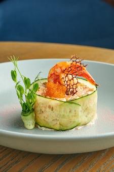 Klassieke salade olivier met huisgemaakte mayonaise, komkommers, ei en garnalen. modern serveren van de chef. salade met zeevruchten. gezond eten