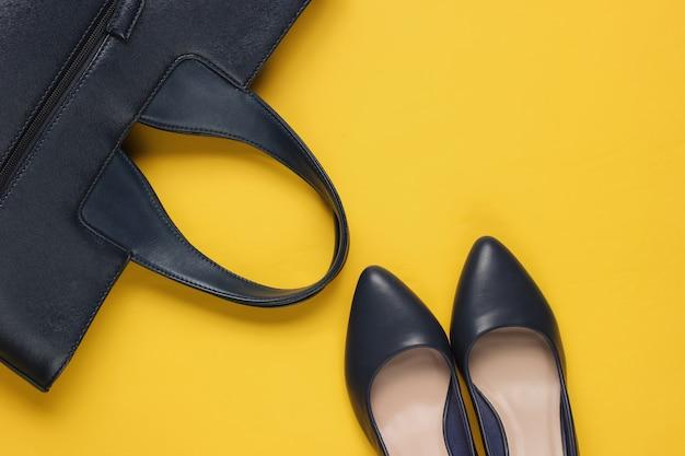 Klassieke schoenen met hoge hakken, lederen tas op geel