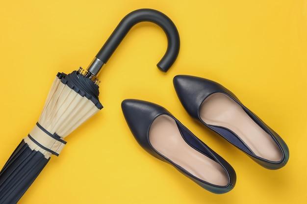 Klassieke schoenen met hoge hakken, paraplu op geel
