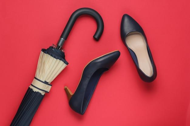 Klassieke schoenen met hoge hakken, paraplu op rood
