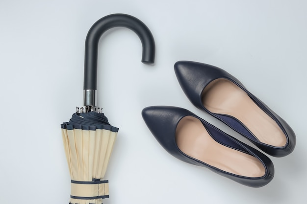 Klassieke schoenen met hoge hakken, paraplu op wit