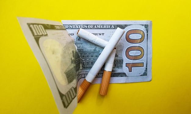 Klassieke sigaretten staan op honderd amerikaanse dollarbiljetten. sigaretten op een biljet van honderd dollar op een gele achtergrond.