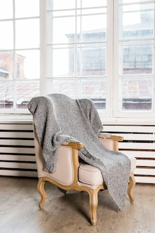 Klassieke stoel op houten vloer met grijze deken in de buurt van groot raam. betrouwbare en comfortabele kamer. landelijke stijl stoel. vintage stijl slaapkamer interieur. stijlvol interieur