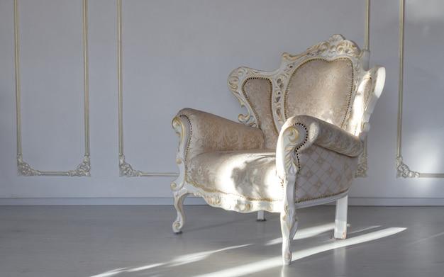 Klassieke stoffen witte fauteuil in witte kamer