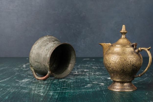 Klassieke theepot en vaas op marmeren tafel.