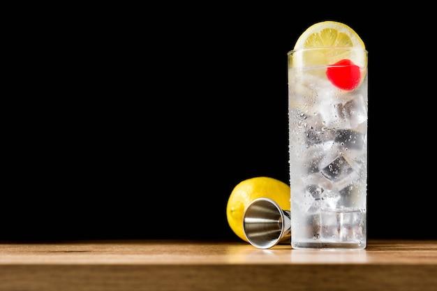 Klassieke tom collins-cocktail op houten lijst en zwart