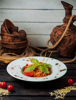 Klassieke tomatenspaghetti gegarneerd met geraspte parmezaanse kaas en verse basilicum
