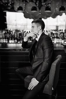 Klassieke trouwfoto. portret van een bruidegom zittend op een stoel bij de bar. low key.