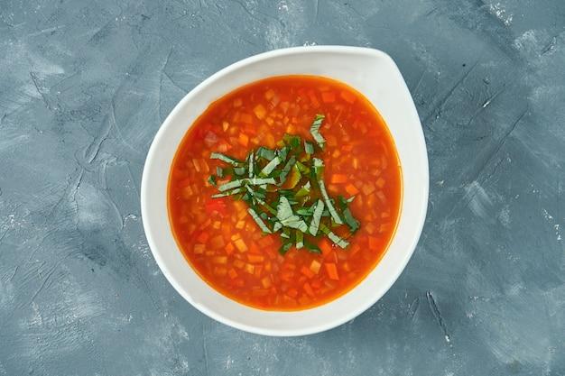 Klassieke vegetarische minestrone groentesoep in een witte kom op een betonnen ondergrond. bovenaanzicht