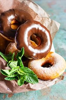 Klassieke verse donuts met suiker en chocoladesuikerglazuur met lavendelbloemen en muntblaadjes