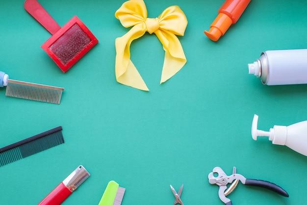 Klassieke verzorgings- en kappershulpmiddelen op een groene achtergrond: vernis, kammen, lotions, borstel, gele strik. bovenaanzicht, cirkellay-out, lay-out, kopieerruimte