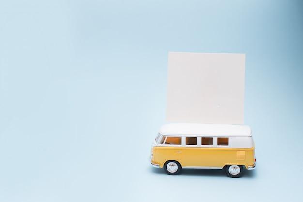 Klassieke vintage gele bus met blanco papieren kaart of notitie, zomerseizoen. concept van bustour