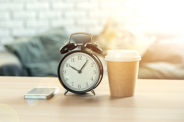 Klassieke vintage wekker en koffiekopje op houten achtergrond
