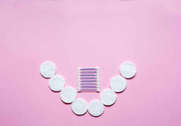Klassieke wattenschijfjes en wattenstaafjes op roze tafel. concept hygiëne, geneeskunde, gezondheidszorg, schoonheid. bovenaanzicht
