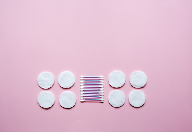 Klassieke wattenschijfjes en wattenstaafjes op roze tafel. concept van hygiëne