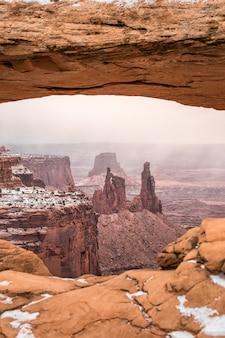 Klassieke weergave van de beroemde mesa arch, symbool van het amerikaanse zuidwesten, in schilderachtig gouden ochtendlicht bij zonsopgang op een mooie winterdag in de winter na zware sneeuwval, canyonlands national park, utah, verenigde staten