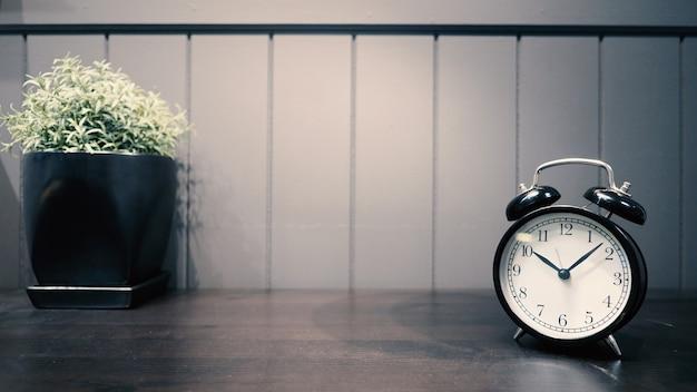 Klassieke wekker in zwarte kleur op de werkende houten tafel en decoratie met kleine boomplant