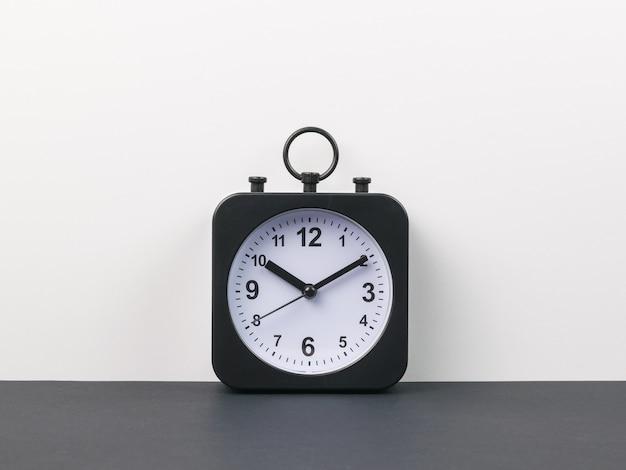 Klassieke wekker met handen op een zwarte en grijze achtergrond. crass wijzerplaat.