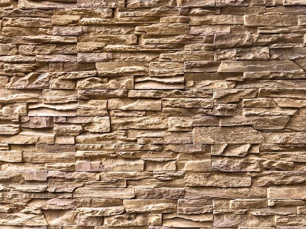Klassieke willekeurige lichtbruine baksteen aan de muur om de buitenkant van het gebouw te versieren.