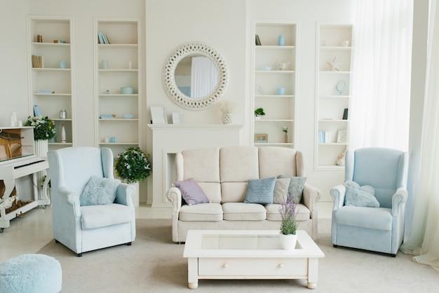Klassieke woonkamer in blauwe en witte tinten. sofa, fauteuils, open haard, salontafel en spiegel in het huis