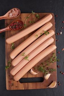 Klassieke worstjes van gekookt vleesvarkensvlees op snijplank met peper en basilicum, peterselie, tijm en kerstomaatjes.