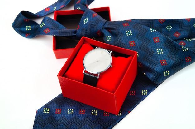 Klassieke zakelijke horloges in rode doos en abstracte blauwe stropdas