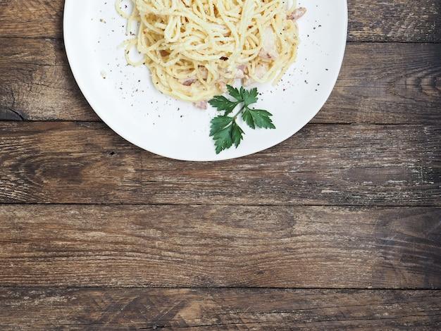 Klassieke zelfgemaakte pasta carbonara. spaghetti met spek, eigeel en parmezaanse kaas op lichte plaat op donkere houten achtergrond.