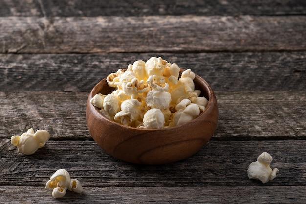 Klassieke zoute popcorn in een houten kom in rustieke stijl.