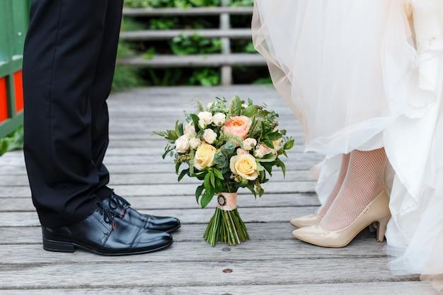 Klassieke zwarte en beige schoenen van bruid en bruidegom met boeket rozen