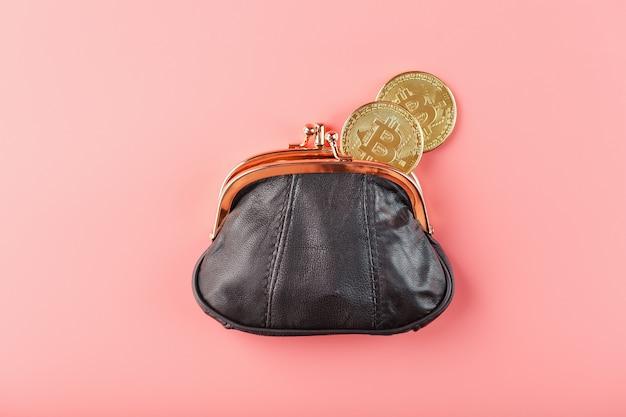 Klassieke zwarte portemonnee met bitcoin munten op een roze muur.