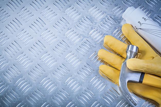 Klauwhamer beschermende handschoenen gerolde technische tekeningen op gegroefde metalen plaat kopiëren ruimte constructie concept