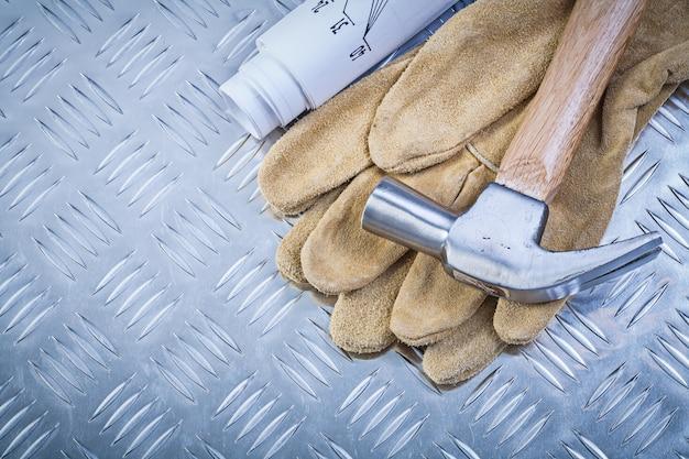 Klauwhamer lederen beschermende handschoenen blauwdrukken op gegroefde metalen plaat constructie concept