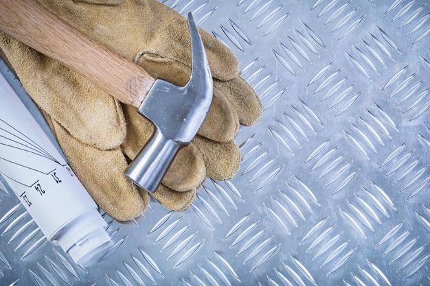 Klauwhamer lederen beschermende handschoenen technische tekeningen op gegroefde metalen plaat bouwconcept
