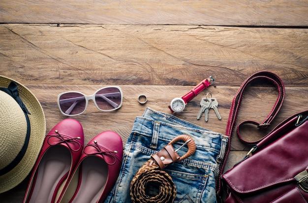 Kleding en accesoires voor vrouwen, geplaatst op een houten vloer.
