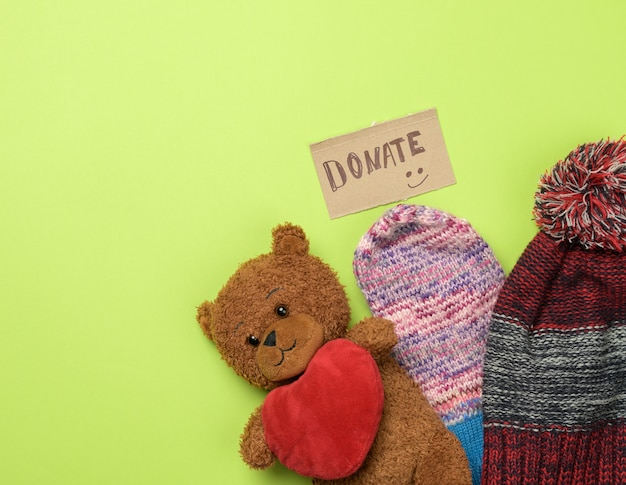 Kleding en bruine teddybeer op een groene achtergrond, bovenaanzicht. concept schenking