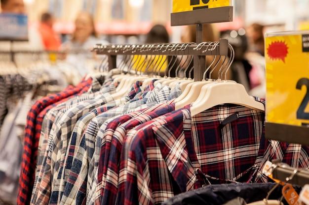 Kleding hangt op een plank. kledinghangers met overhemden. stijlvolle herenkleding
